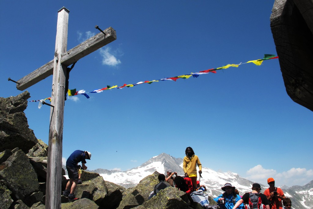 A cross and Tibetan prayer flags on the Krimmler Tauern alpine pass.