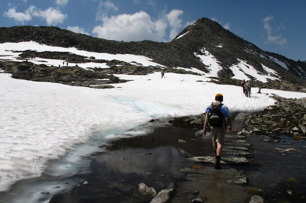 Hiking over snow and water in high alpine regions.