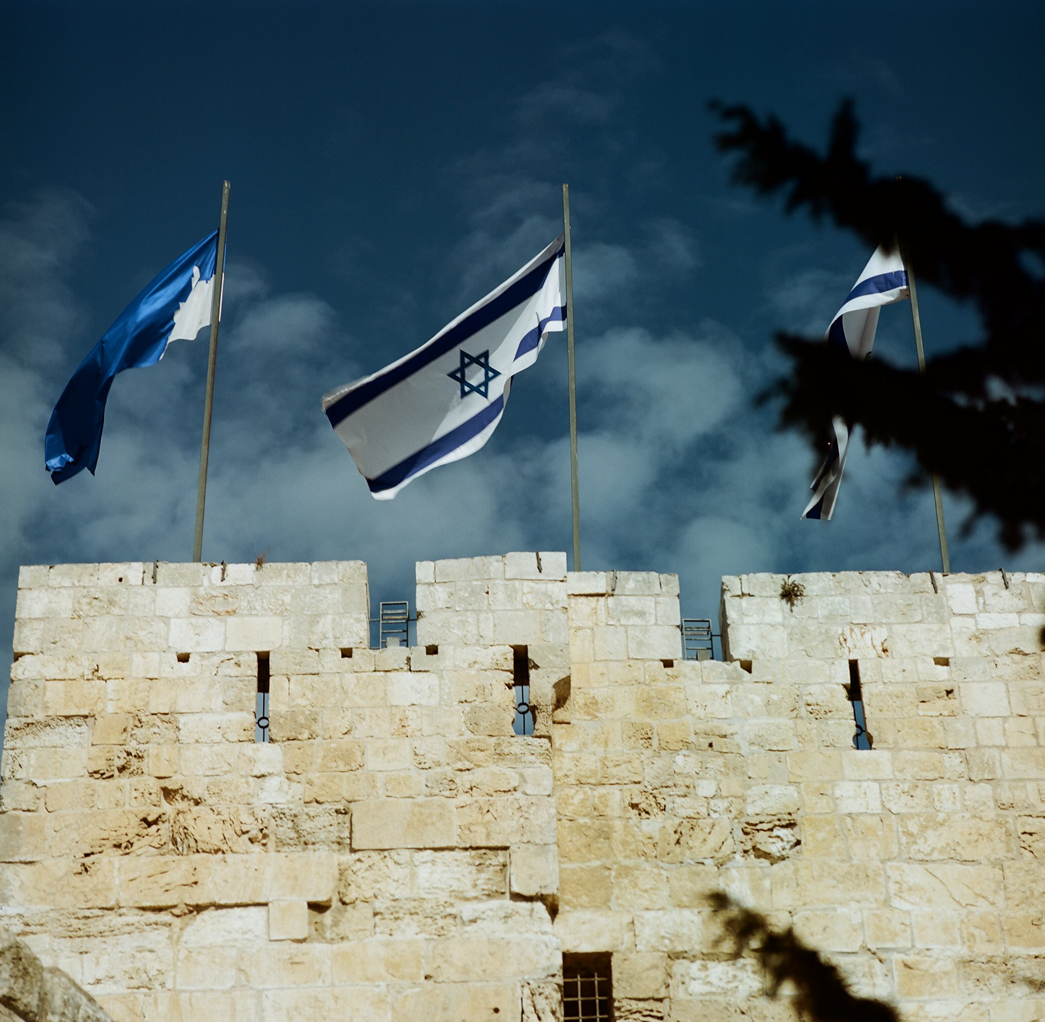 Flags of Israel and the City of Jerusalem atop David's Tower, part of the Ottoman city walls of Jerusalem.