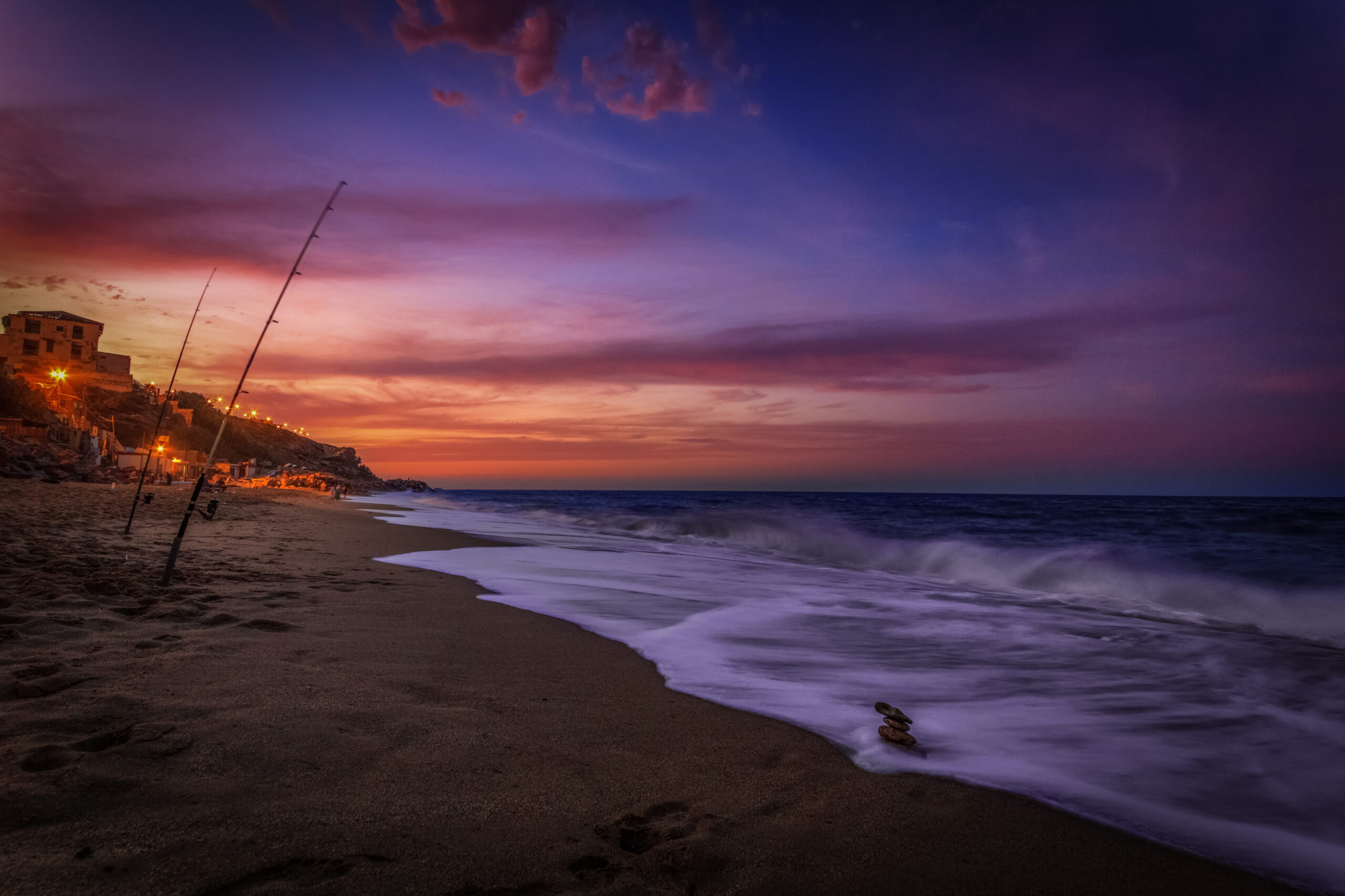 Blue Hour/Twilight photo of a beach, the ocean and dark-red and blue skies at Aïn Taya beach, Algeria